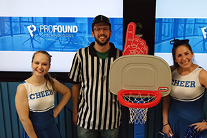 Two female employees dressed as cheerleaders on either side of male employee dressed as basketball ref in front of two television displays