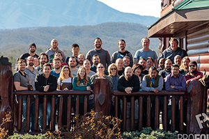 Entire company team members posing infront of mountain range next to cabin