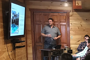 West coast sales team member giving presentation in cabin basement
